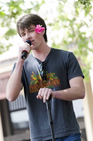 Patrick Collins, 21, dons a flower thrown to him by fans while singing at De Anza's Club Karaoke day in the main quad, Thursday April 17.